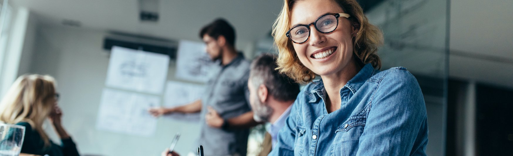 LP_Header-1748x534-smiling-white-woman-glasses-conference-room-office