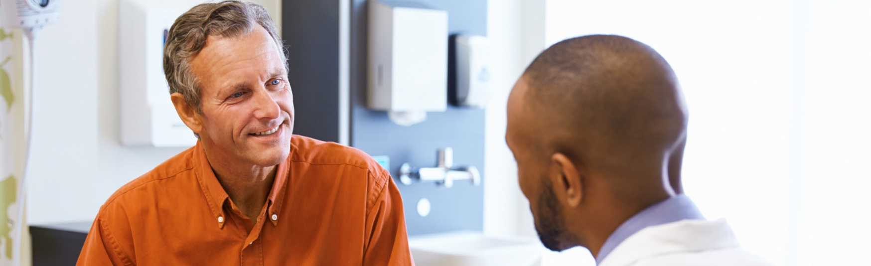 LP_Header-1748x534-african-american-doctor-white-male-patient-consultation-office-conversation-similing